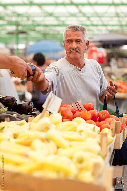 Old man buying fruits and vegetables at the local market. by Mosuno for Stocksy United