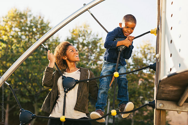A 5 years old boy playing with his mother at the playground. by BONNINSTUDIO for Stocksy United