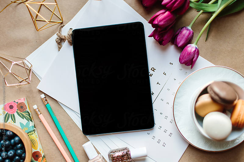 A smart touch tablet on a table with a calendar by Kristen Curette Hines for Stocksy United