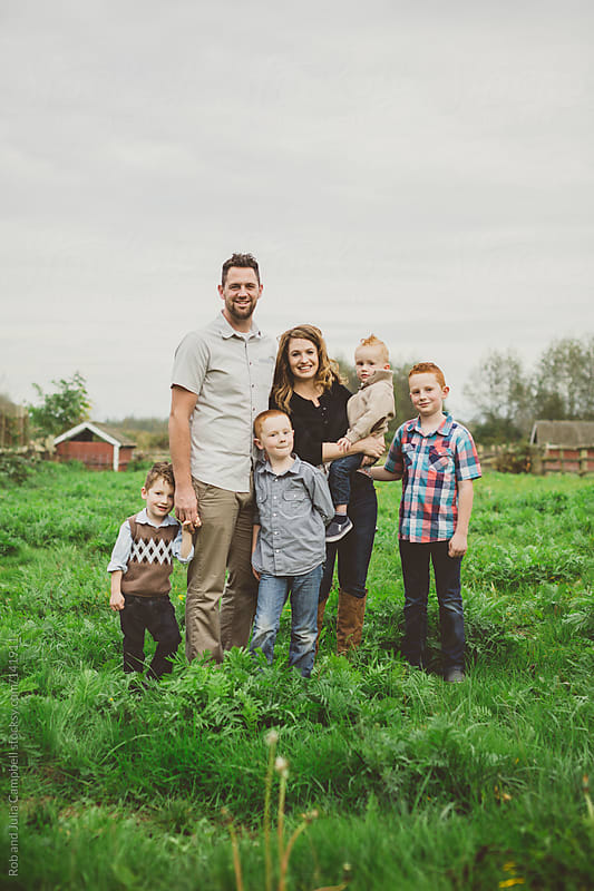 Young family posing for family portrait in farmers field by Rob and Julia Campbell for Stocksy United