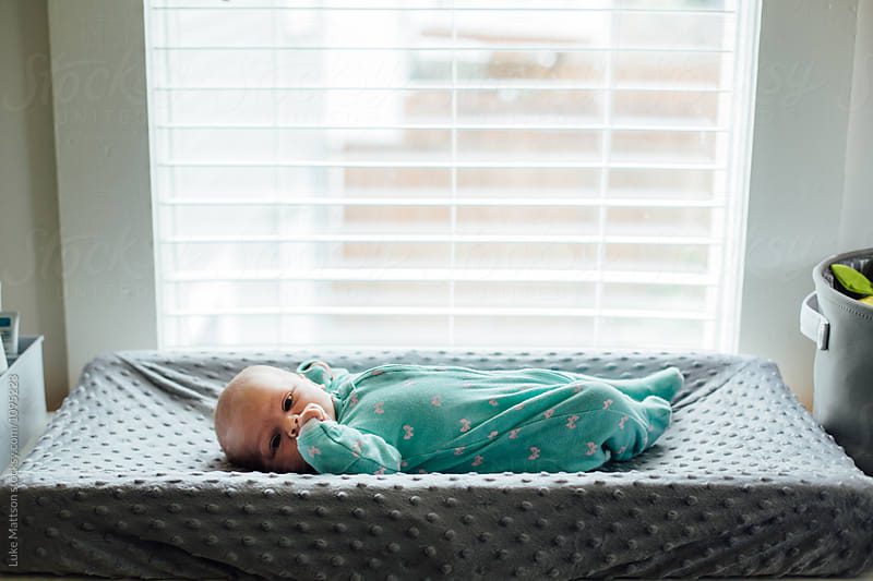 Newborn Baby Girl In Green Onesie Lying On Changing Table Under Big Window by Luke Mattson for Stocksy United