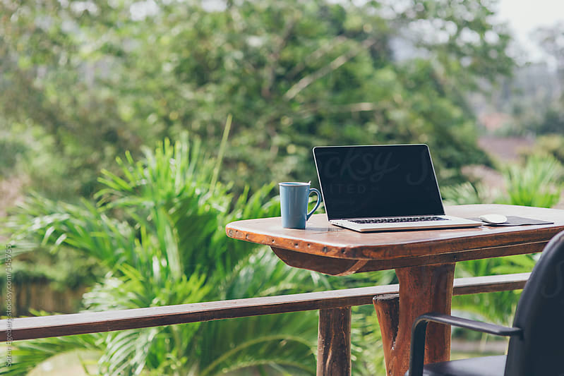 Outdoor nature office with laptop computer on wooden desk and chair with green tropical view by Soren Egeberg for Stocksy United