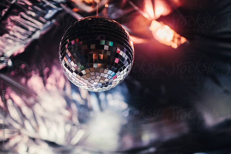 Disco ball hanging from the ceiling of a house party by Kristen Curette Hines for Stocksy United