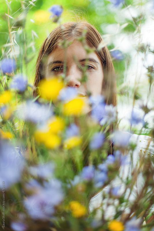 Springtime queen: young woman looks at camera through mixed wildflowers bouquet by Laura Stolfi for Stocksy United