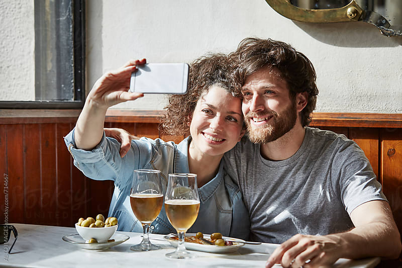 Happy Couple Taking Selfie In Restaurant by ALTO IMAGES for Stocksy United