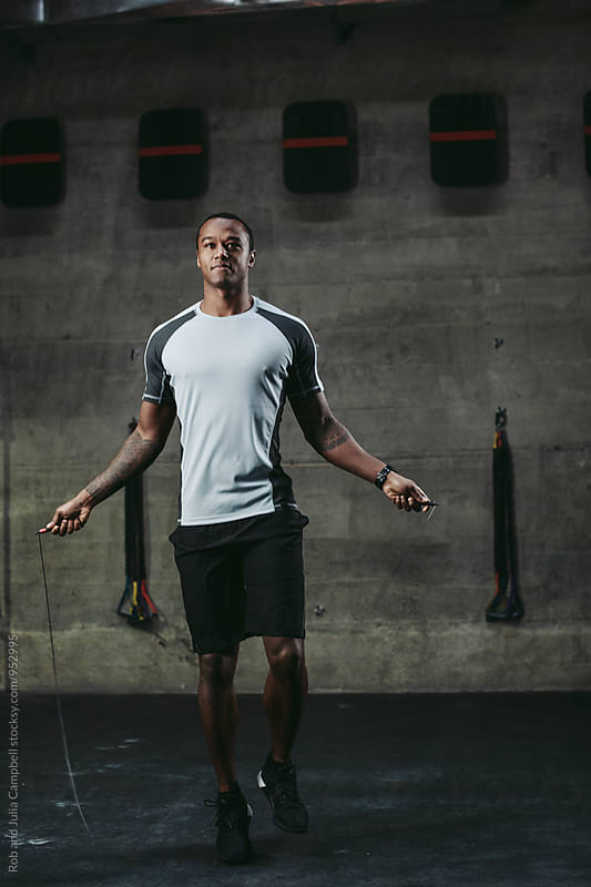 Young, fit black man training hard in fitness gym - skipping by Rob and Julia Campbell for Stocksy United