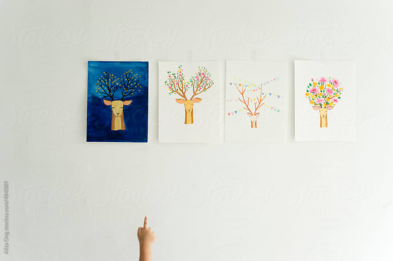 Baby's finger pointing at nursery painting by Alita Ong for Stocksy United