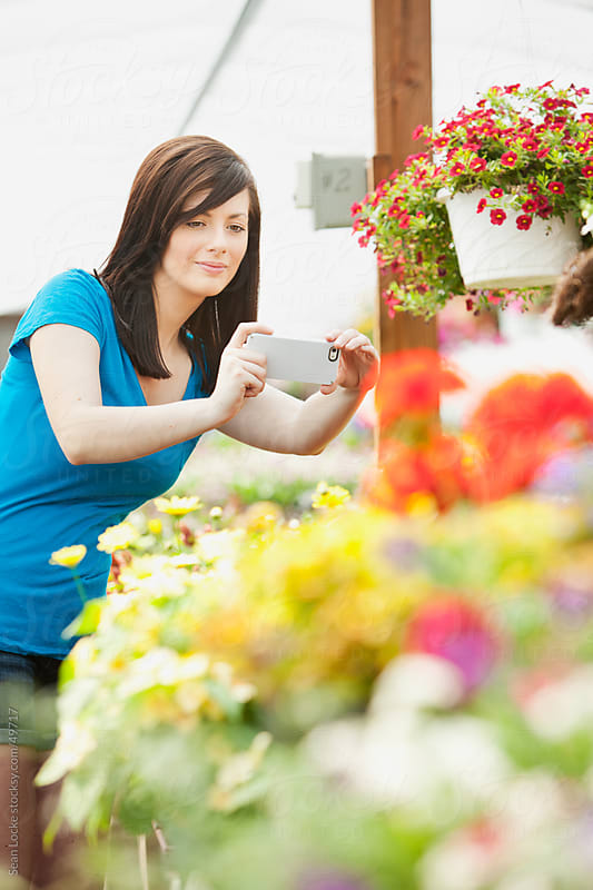 Nursery: Woman Shoots Picture of Flowers by Sean Locke for Stocksy United