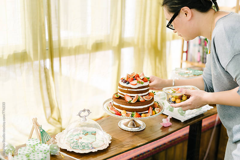 Young woman preparing cake for a party by Maa Hoo for Stocksy United