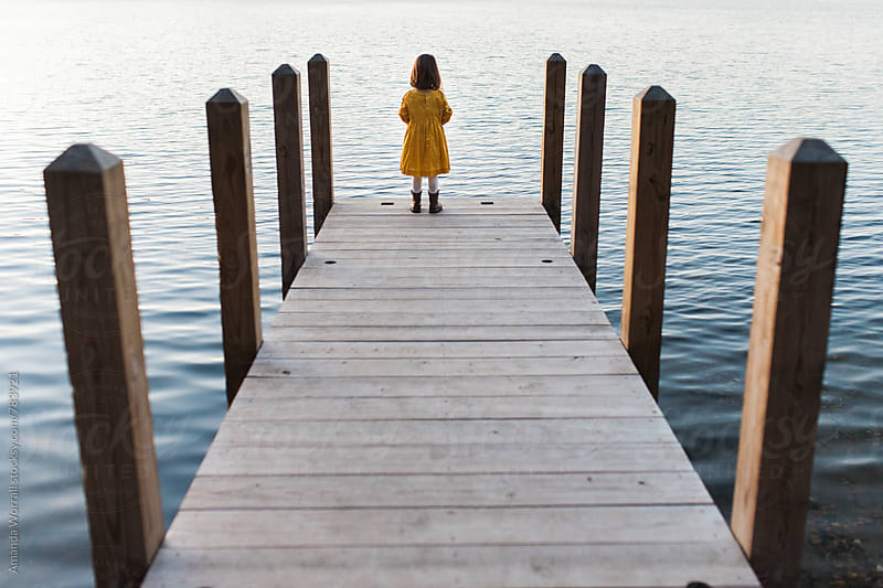 Girl looking out at a lake at the end of a dock by Amanda Worrall for Stocksy United