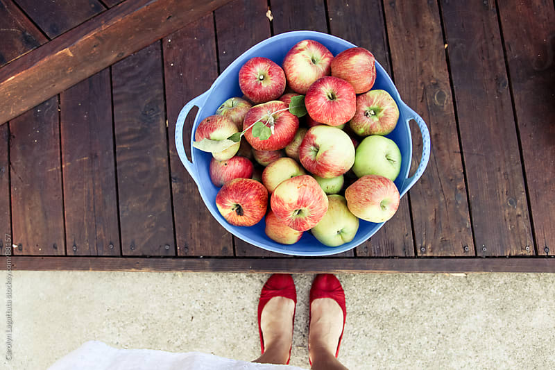 A girl in red flats with her apple bounty by Carolyn Lagattuta for Stocksy United