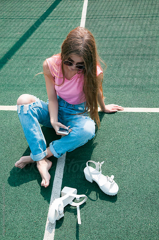 girl with cellphone on the school sport field  by Alexey Kuzma for Stocksy United
