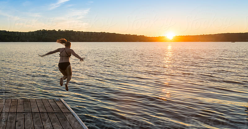 Woman Jumping Into Warm Summer Cottage Lake At Sunset from Dock by JP Danko for Stocksy United