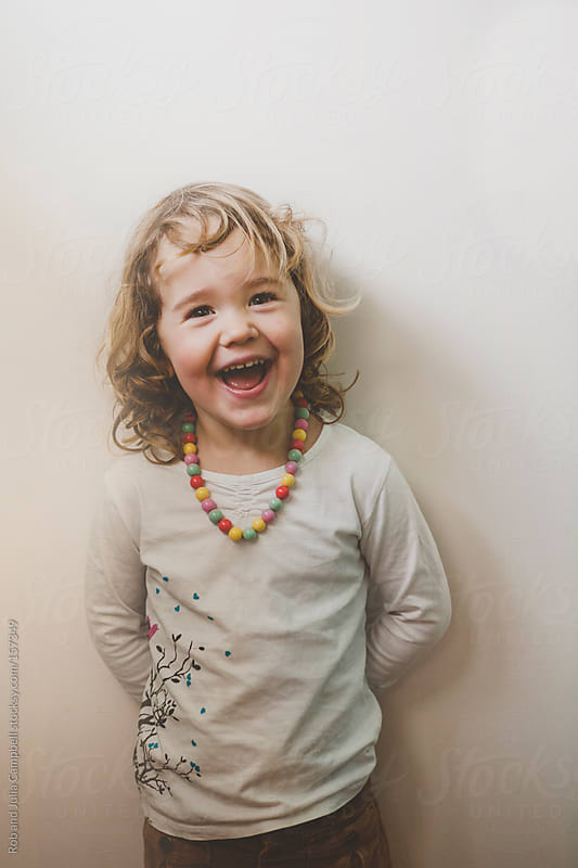 Cute toddler girl laughing on white background (door) by Rob and Julia Campbell for Stocksy United