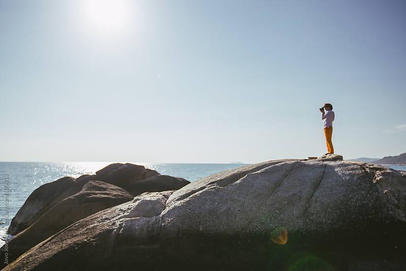 Summertime - photographer standing on a big rock and taking a photo by Jovo Jovanovic for Stocksy United