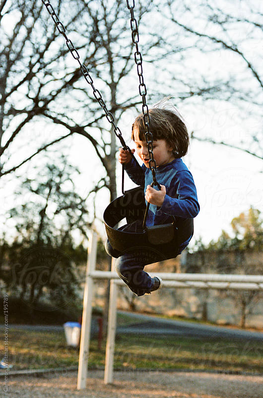 Boy swinging in the late afternoon (Film)  by Cameron Whitman for Stocksy United