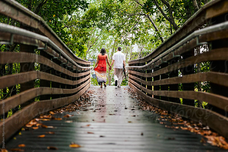Couple Holding Hands on Boardwalk by Stephen Morris for Stocksy United