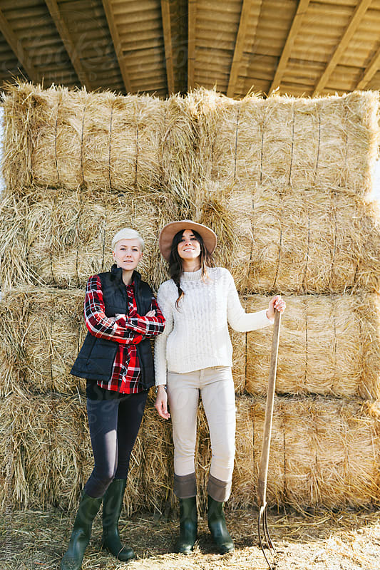 Portrait of a women farmers standing in front of a haystack. by BONNINSTUDIO for Stocksy United