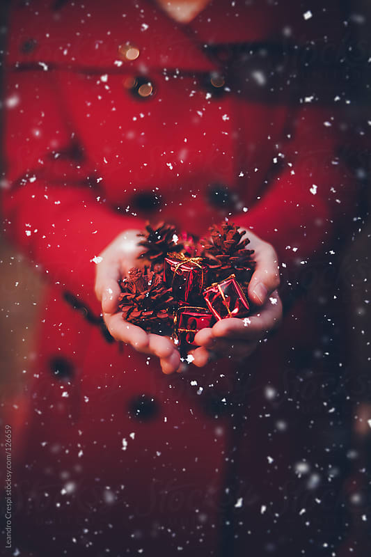 hands holding christmas decoration while snowing by Leandro Crespi for Stocksy United