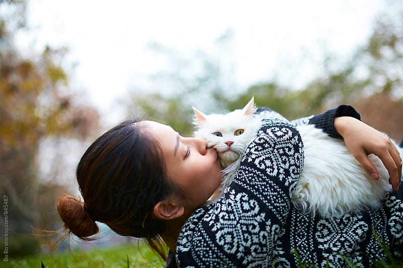 happy young asian woman with her cat outdoor by Bo Bo for Stocksy United