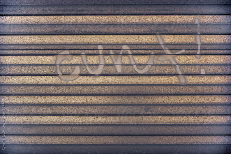 The word 'cunt' graffitied on garage door by Rowena Naylor for Stocksy United