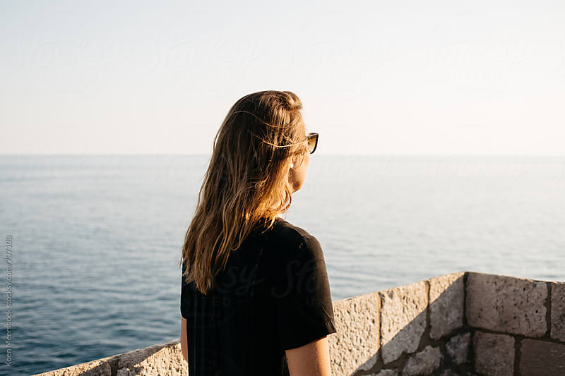 Young woman on a viewpoint at the seaside by Koen Meershoek for Stocksy United
