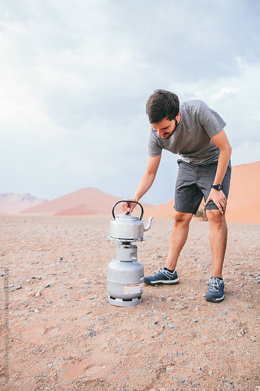 Man heating a pot of coffee on a camping gas stove gas cooker in the middle of the desert by Alejandro Moreno de Carlos for Stocksy United
