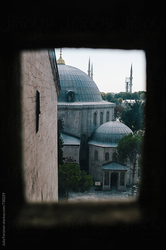 Buildings in Sultanahmet, Istanbul seen through a small window in the Hagia Sophia. by Julia Forsman for Stocksy United