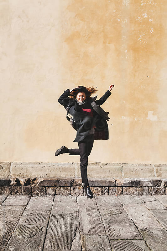 Teen Girl with Coat and Hat Jumping on a Grungy Background by Giorgio Magini for Stocksy United