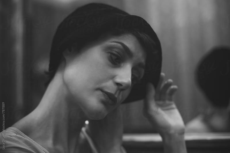 Portrait of a beautiful pensive woman wearing a vintage black bonnet by Luca Di Lotti for Stocksy United