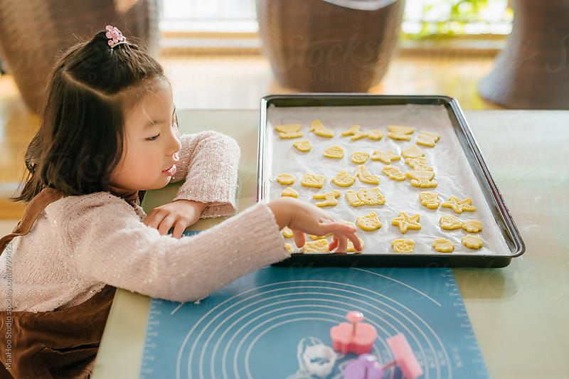 Little girl looking at unbaked biscuits by Maa Hoo for Stocksy United