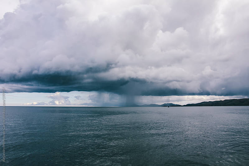 Rain storm and clouds over lake by Alejandro Moreno de Carlos for Stocksy United