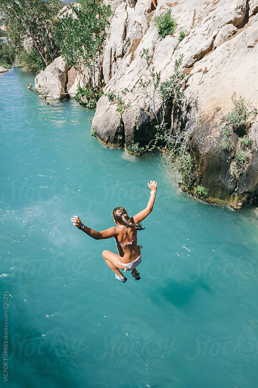 Girl Jumping into the River by VICTOR TORRES for Stocksy United