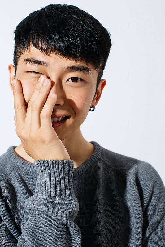 Portrait of a young asian man smiling over white background.  by BONNINSTUDIO for Stocksy United