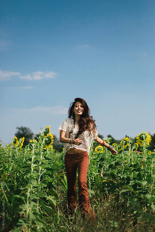 Happy Woman Running through the Field of Sunflowers by Marija Savic for Stocksy United