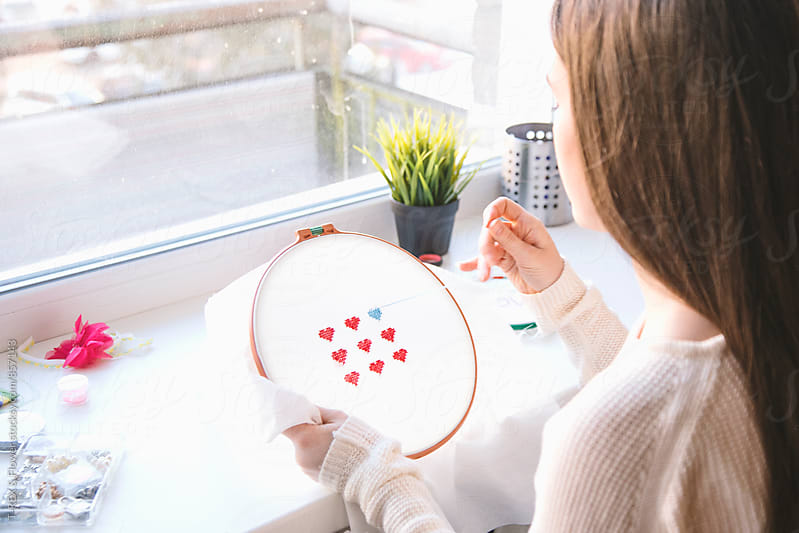 Young woman embroidering small red hearts by Danil Nevsky for Stocksy United