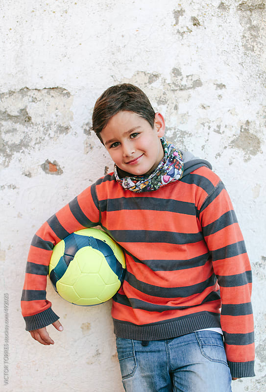 Portrait of a Cute Kid with a Soccer Ball by VICTOR TORRES for Stocksy United