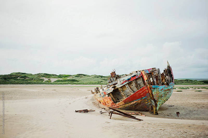 Colourful shipwrecked wooden boat decaying on a sandy beach by Suzi Marshall for Stocksy United