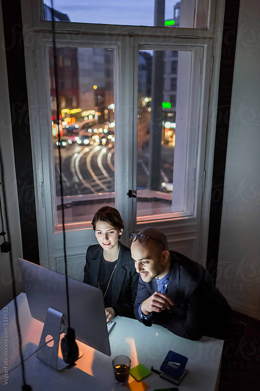 Two Young Business People Working Late by VegterFoto for Stocksy United