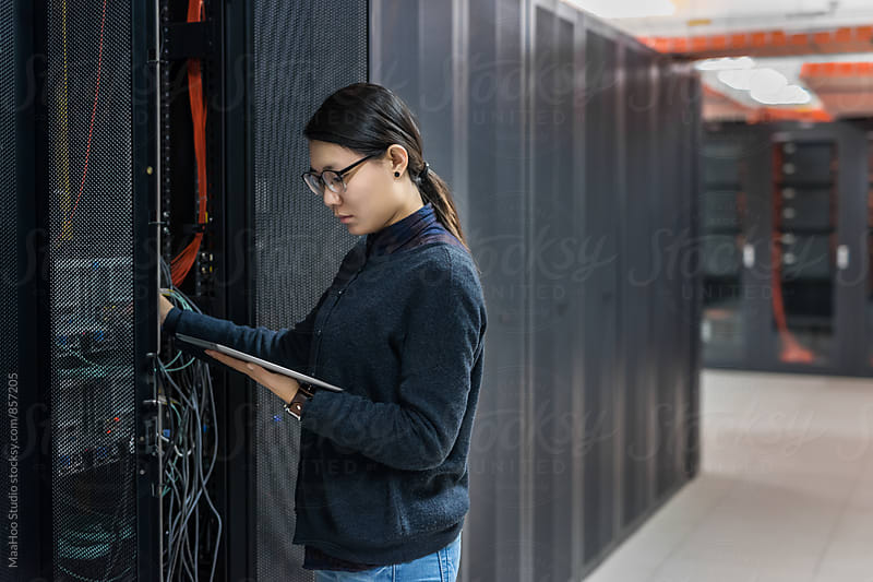 Female technician working in data center by Maa Hoo for Stocksy United