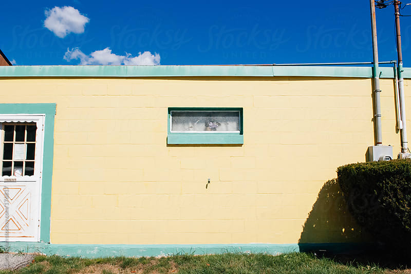 Yellow concrete building with light green trim by Cara Dolan for Stocksy United