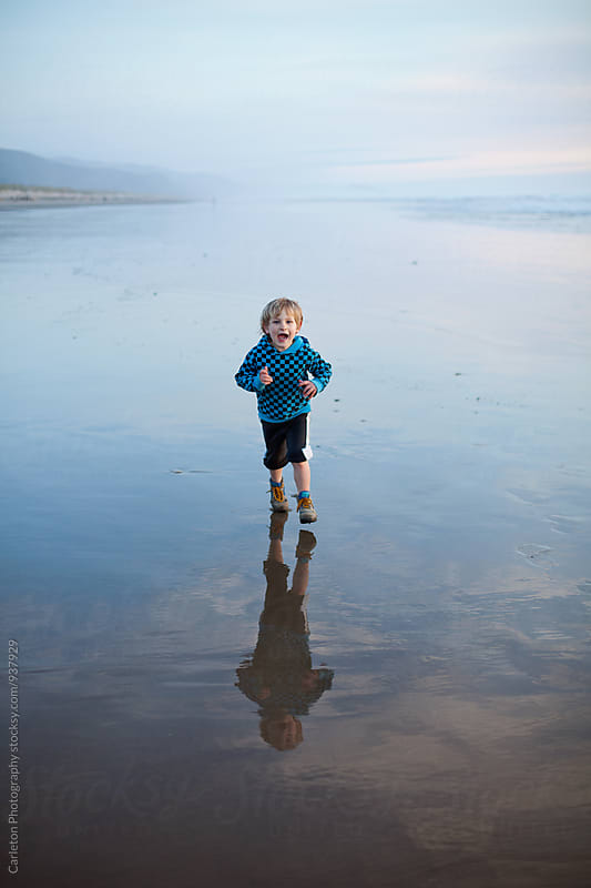 Happy boy running on the beach  by Carleton Photography for Stocksy United