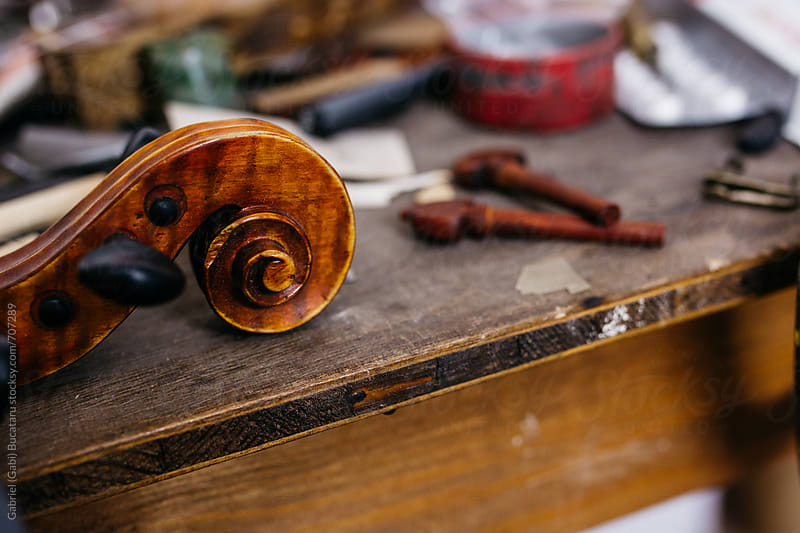 Violin scroll and pegs on a workbench by Gabriel (Gabi) Bucataru for Stocksy United