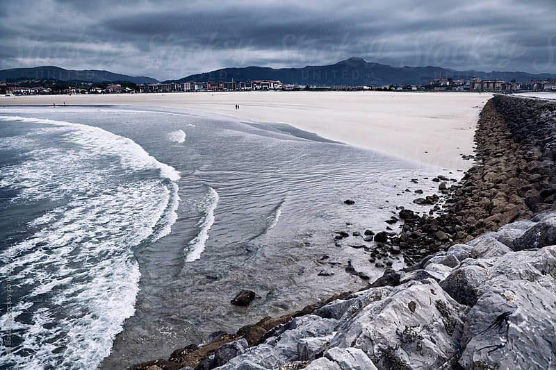 Hendaye beach seen from the seawall by Ivan Bastien for Stocksy United