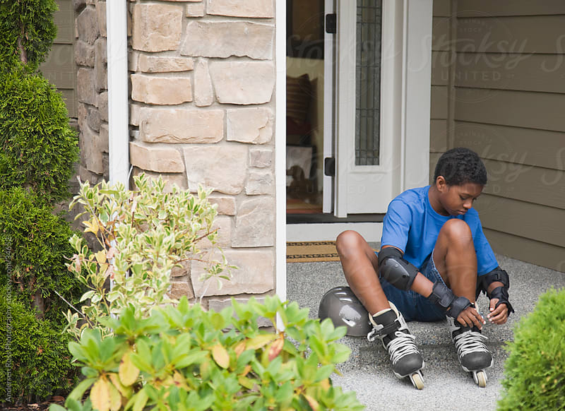 Boy (10-11) fastening inline skates in front of house by Andersen Ross Photography for Stocksy United