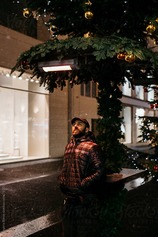 Man looking up at the decorations in the snowing  city at Christmas time by Beatrix Boros for Stocksy United