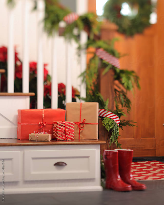 Red boots and Christmas gifts in home entry by Daniel Hurst for Stocksy United