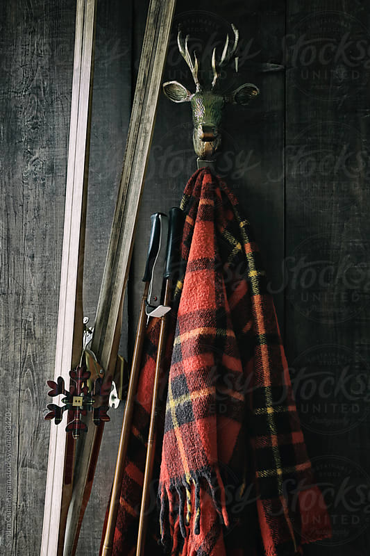 Skis and poles leaning against plaid blanket by Sandra Cunningham for Stocksy United