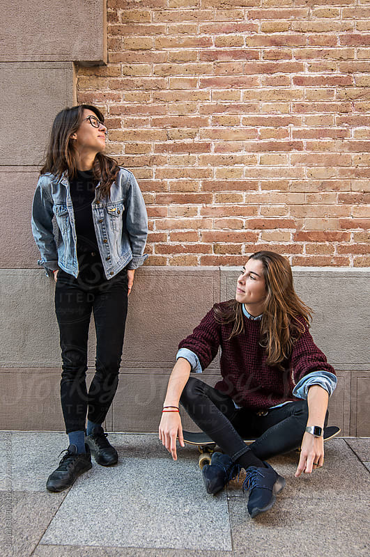 Two young skater girls taking a break in front a wall  by Bisual Studio for Stocksy United