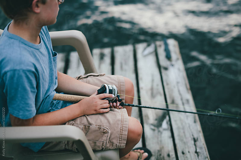 boy sitting on a dock fishing  by Kelly Knox for Stocksy United